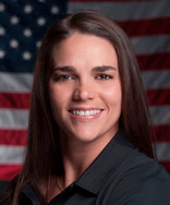 Headshot of Emily in front of an American flag